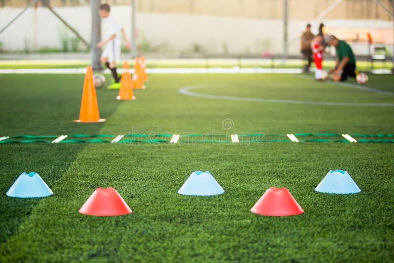 Marker Cone sobre el césped artificial verde con simulacros de escalera borrosa y jugadores de fútbol infantil están entrenando a fotos de archivo libres de regalías