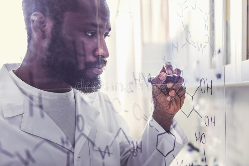 Chemist holding marker pen writing molecular formula. Marker pen. Professional promising chemist feeling busy while holding black marker pen writing molecular royalty free stock images