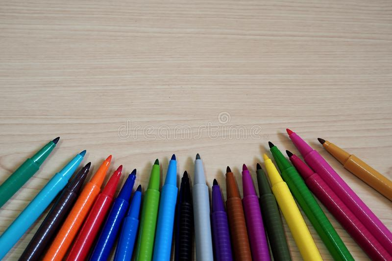 Marker Pens on wooden table background. Colorful water Marker Pens put on wooden table background with space for using stock photos