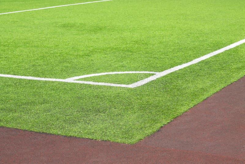 Markera vit målarfärg av ett hörn på en grön gräsmatta av fotbollfältet arkivfoto