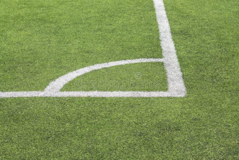 Markera vit målarfärg av ett hörn på en grön gräsmatta av fotbollfältet arkivbild