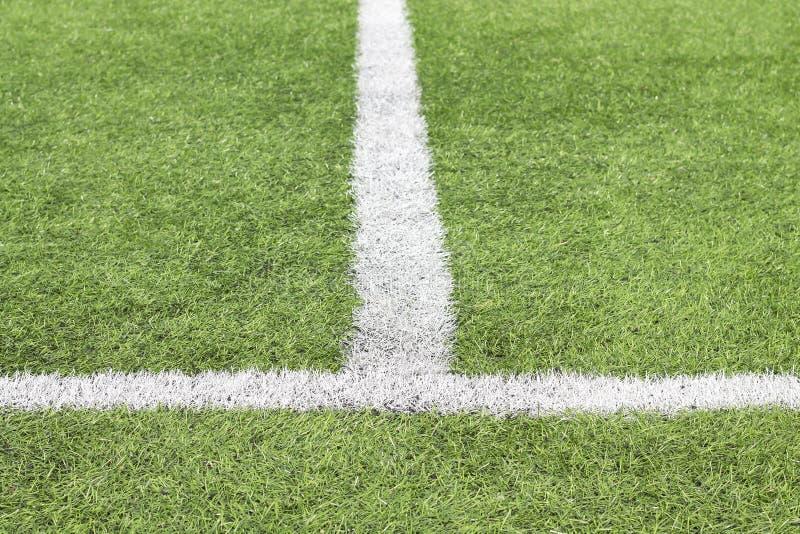 Markera vit målarfärg på ett grönt gräs av fotbollfältet arkivbilder