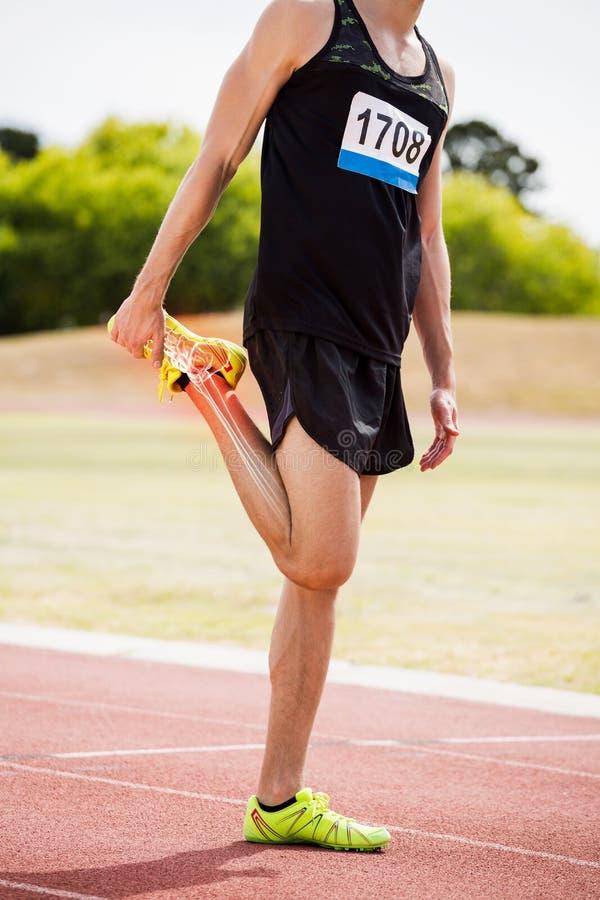 Markerade ben av idrottsman nen man sträckning på loppspår fotografering för bildbyråer