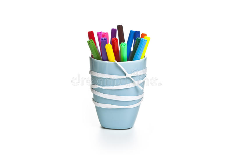 Markers in a ceramics cup with tape. Markers in a blue ceramics cup with tape on the white background stock photos