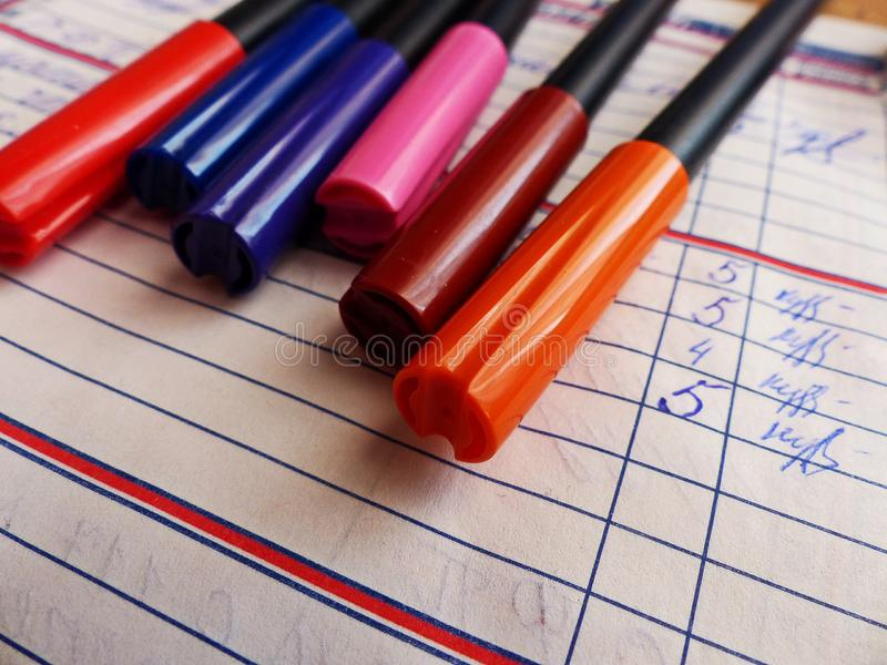 Markers for drawing lie on the diary. Paper diary of a second grade student. Primary school. Retro. Closeup. royalty free stock images
