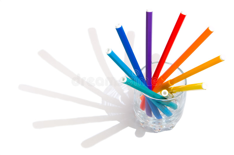 Markers in a glass. The coloredl pencils in a glass on the white background royalty free stock photos