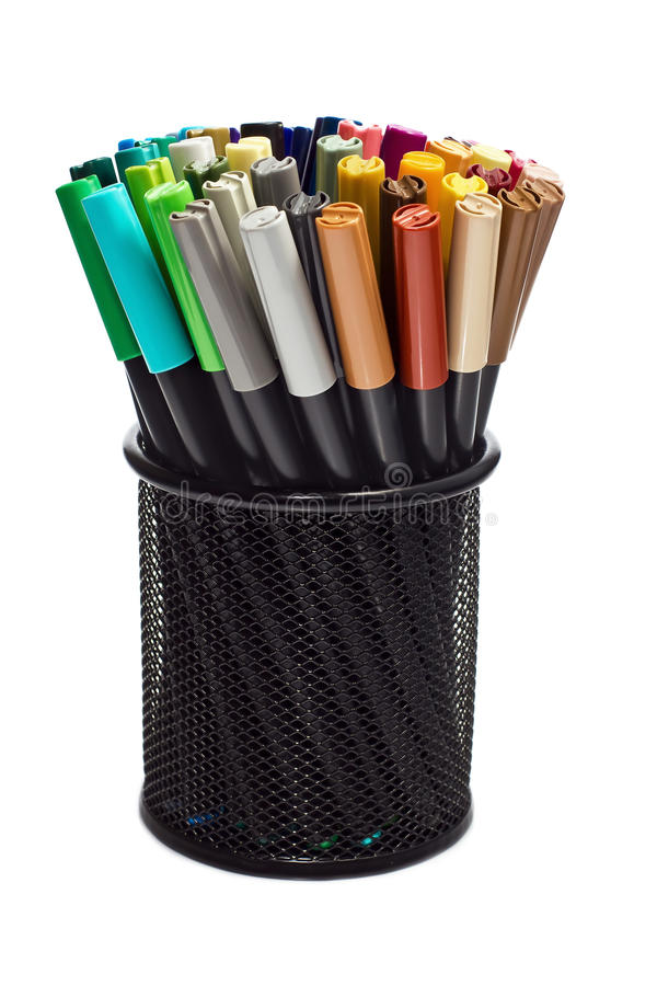 Markers in pencil holder. A selection of colored markers in a pencil holder stock photo