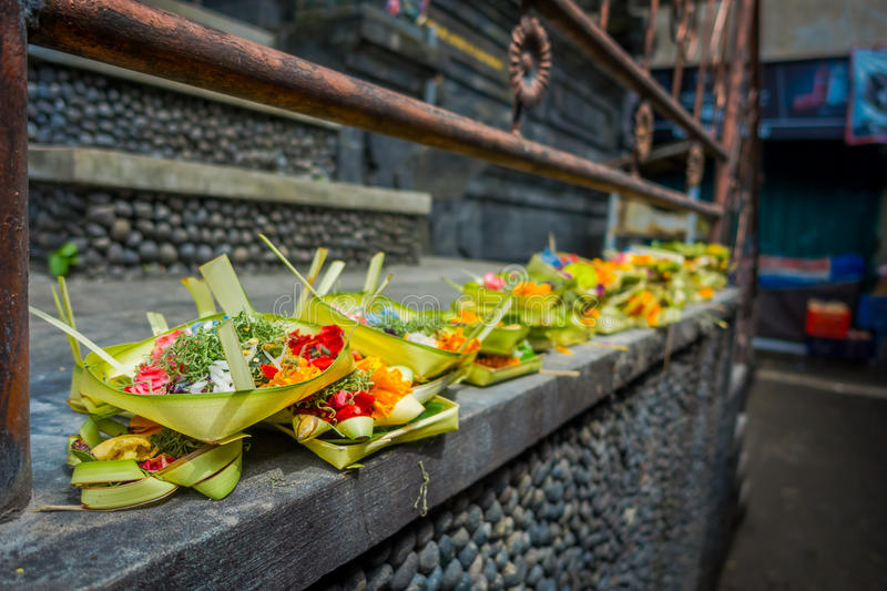 A market with a box made of leafs, inside an arrangement of flowers on a stone table, in the city of Denpasar in stock image