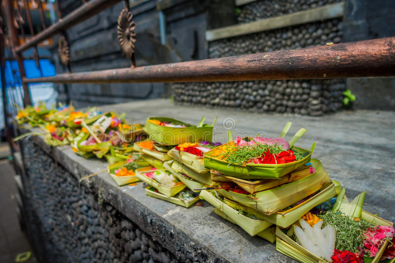 A market with a box made of leafs, inside an arrangement of flowers on a stone table, in the city of Denpasar in royalty free stock photo