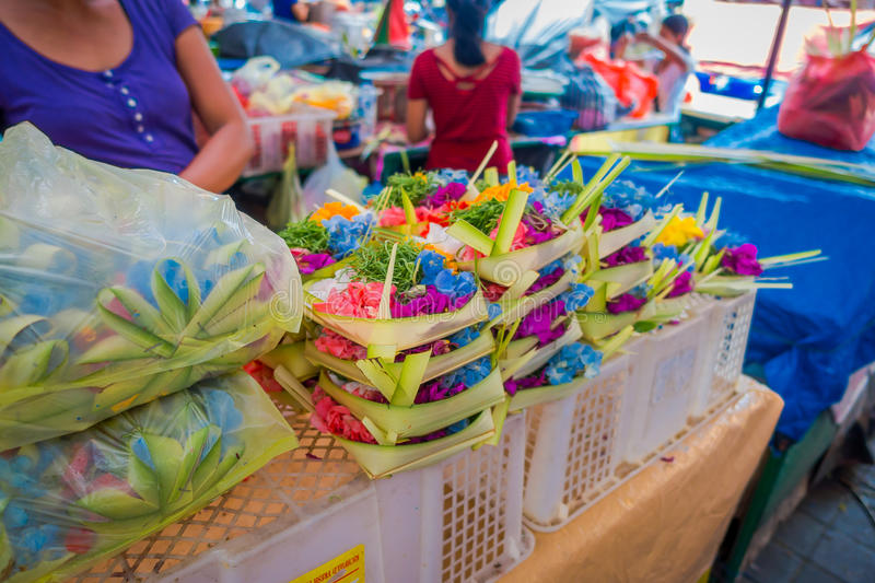 A market with a box made of leafs, inside an arrangement of flowers on a table, in the city of Denpasar in Indonesia royalty free stock photo