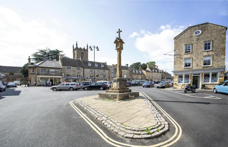 Stow on the Wold Market Cross Looking towards parish church. The market cross in the centre of Stow-on-the-Wold in the Cotswolds with the tower of St Edward`s royalty free stock images