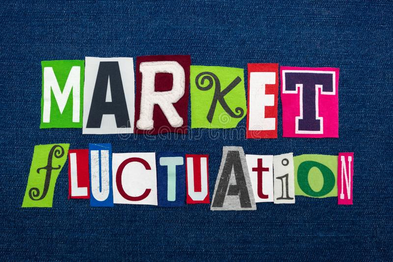 MARKET FLUCTUATION text word collage, multi colored fabric on blue denim, stocks price changes concept stock image