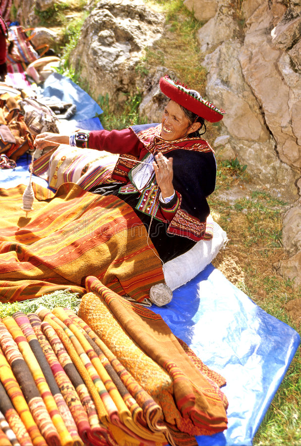 Market-Peru. Traditionally dressed woman selling blankets at the Quechua market in Incan town of Chincero- Sacred Valley, Peru