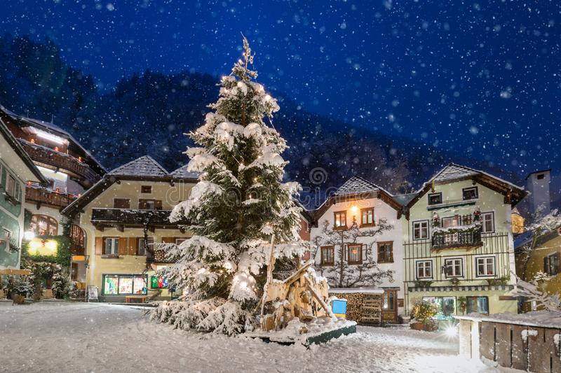 The market place of Hallstatt, Austria in winter time. The market place of Hallstatt, Austria, with a Christmas tree and falling snow in winter time royalty free stock photo