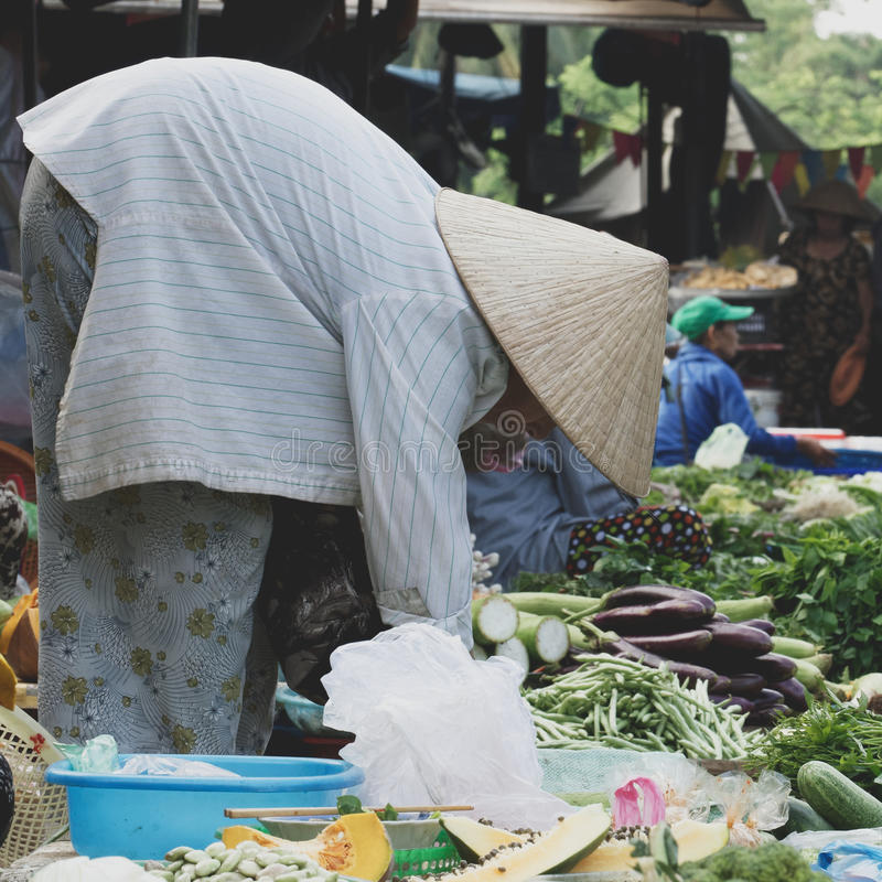Market seller in Hoi An in Vietnam. A market seller laying out their produce on an outdoor market in Hoi An, Vietnam stock image