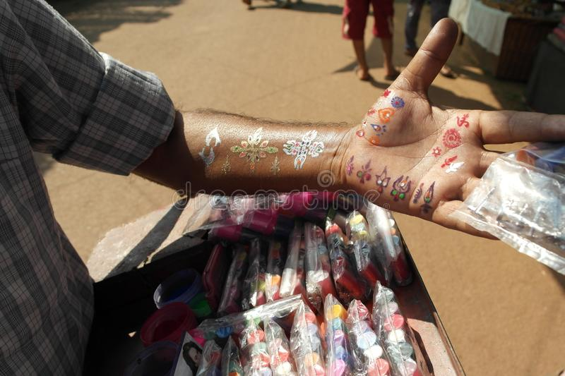Market seller of next-to-skin paints. The market seller of paints for tattoos shows patterns stock image