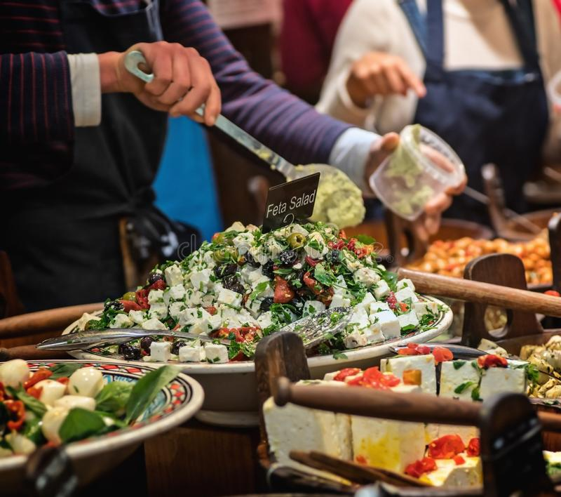 Market seller`s hand holding a plastic box into which Feta salad is placed. Close view royalty free stock photography