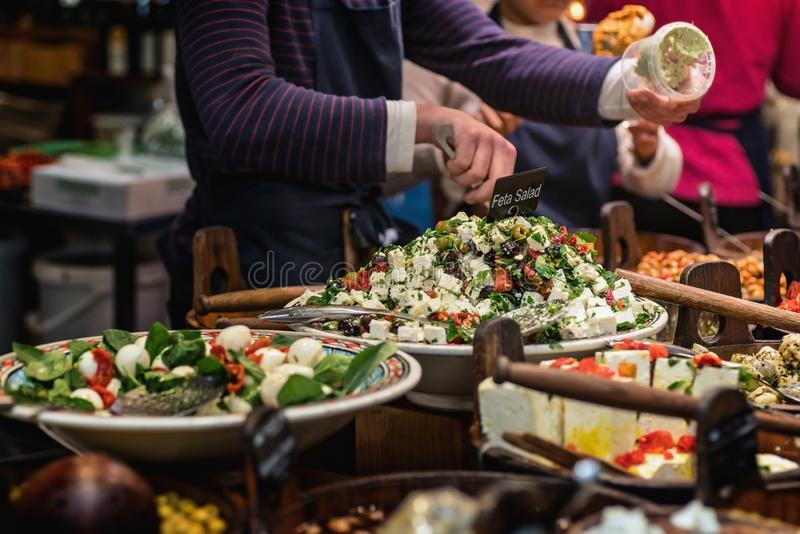 Market seller`s hand holding a plastic box into which Feta salad is placed. Close view stock photography