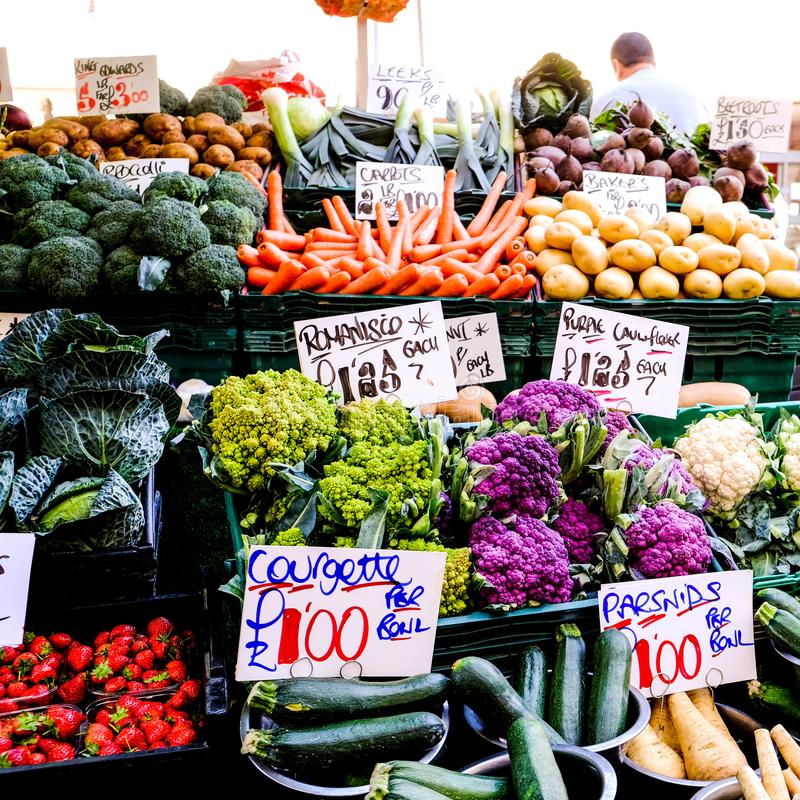 Market Seller Selling Fresh Vegetables. Including Romanisco, Purple Cauliflower, Courgettes, Carrots, Potatoes, Cabbage, Parsnips and Beetroot royalty free stock photography