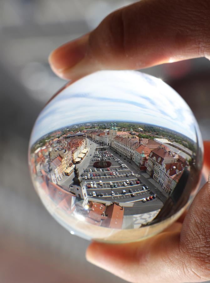 Market square of Hradec Kralove in lens ball which photographer is holding in fingers. Crystal ball wih recletion of Hradec. Kralove in morning royalty free stock images
