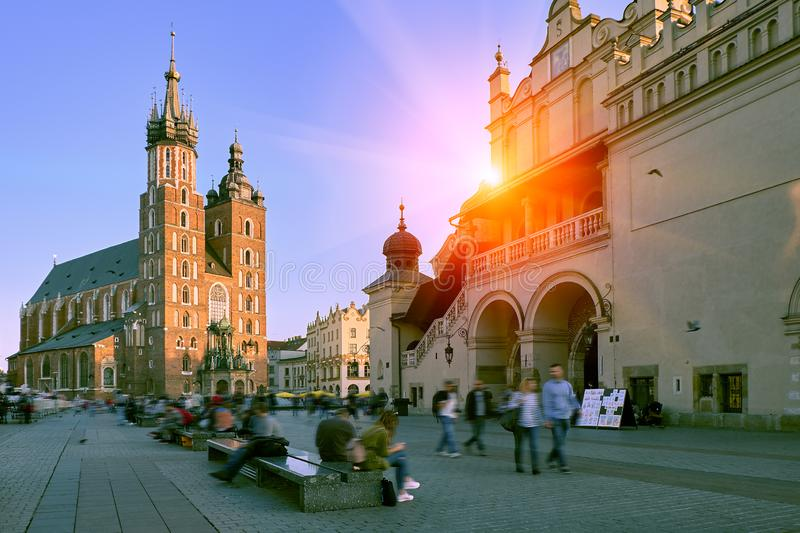 Market square and St. Mary`s Basilica in Krakow, Poland in stunning sunset sun light. People tourists walking down the street and stock photography