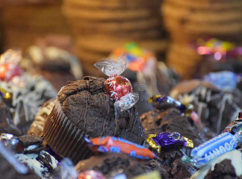 Chocolate muffins. A market stall full of sweet sugary snacks with a focus on one of the decadent chocolate muffins made with branded chocolates / candies. UK stock photo