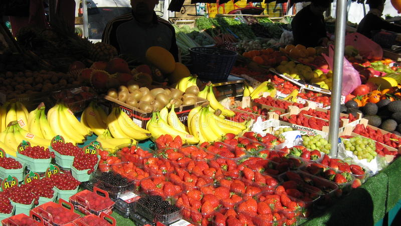 Market stall selling fresh fruit. Fruits as strawberries, bananas, grapes,red currants for sale in the Bastille market in Paris royalty free stock images