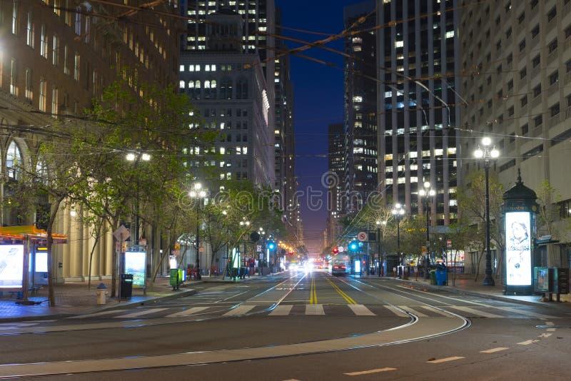 Market Street con él es líneas y rascacielos de la tranvía en la oscuridad en San Fransisco, los E.E.U.U. foto de archivo