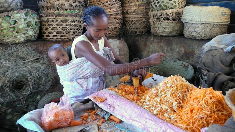 Market. Toliara. Madagascar. Toliara, Madagascar: A woman with her child on her back scratching carrot in the market of Toliara stock photography