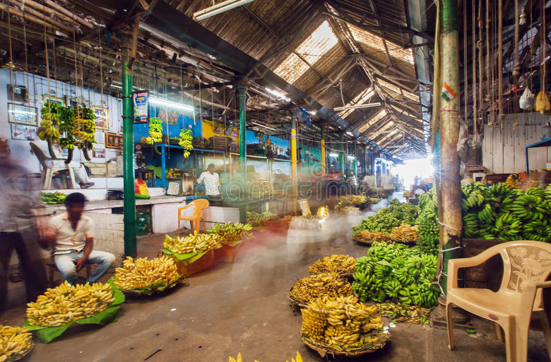 Market traders and buyers walk in motion blur in a storehouse with bananas and fruits. BANGALORE, INDIA - FEB 16: Market traders and buyers walk in motion blur royalty free stock photo
