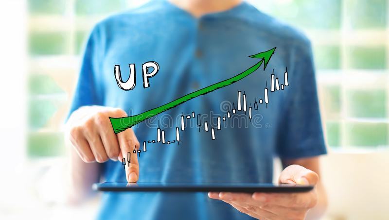 Market up trend chart with man using a tablet royalty free stock image