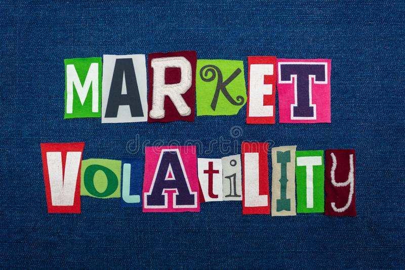 MARKET VOLATILITY text word collage, multi colored fabric on blue denim, unpredictable market direction concept. Horizontal aspect stock photo