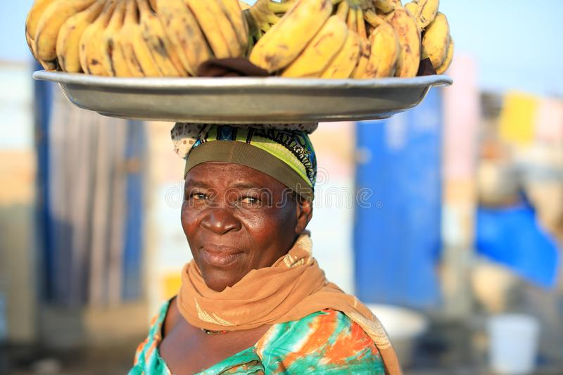 A market woman in Accra, Ghana. A market woman carries a plate with bananas on her head in Accra, Ghana royalty free stock images