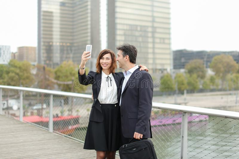 Marketer man and HR manager woman using smartphone taking sel stock photography