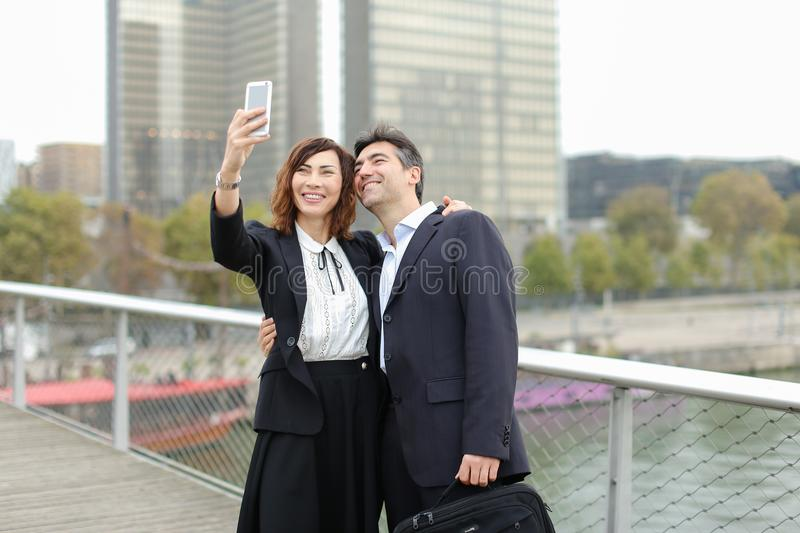 Marketer man and HR manager woman using smartphone taking sel stock images