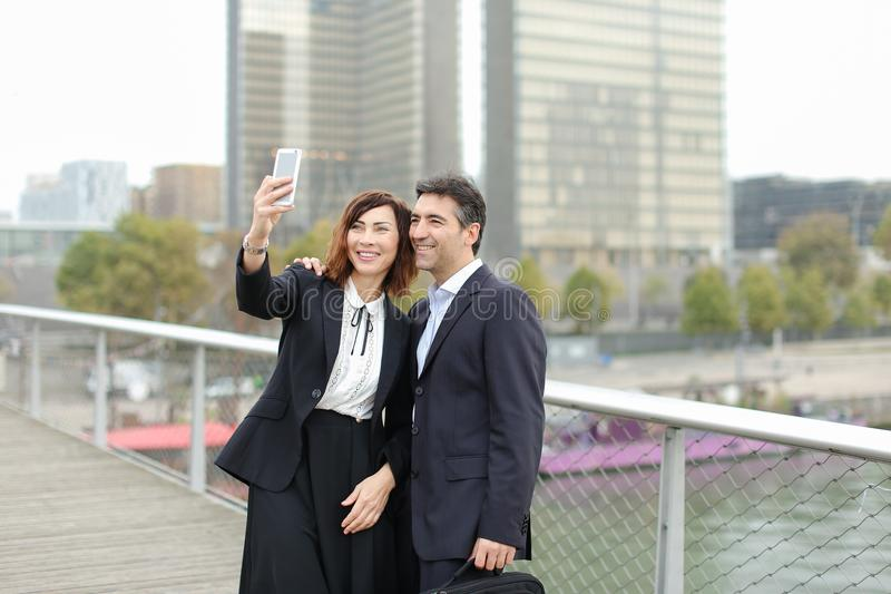 Marketer man and HR manager woman using smartphone taking sel stock photos