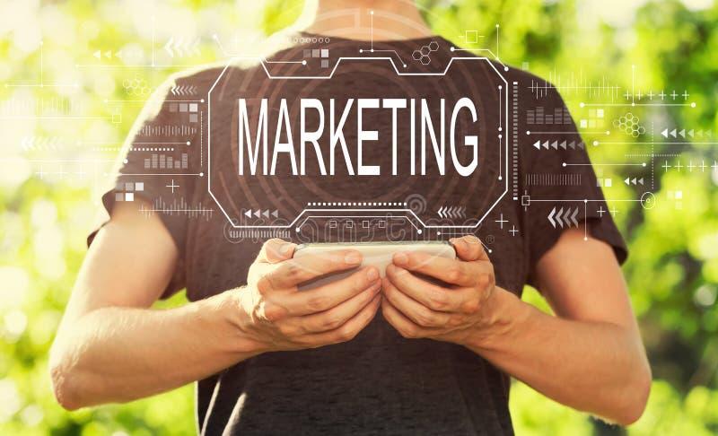 Marketing concept met de mens die zijn smartphone houden stock afbeelding