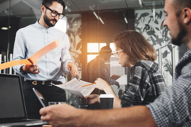 Marketing group discussing new product plan. Young businesspeople working on modern devices. New startup company. Intentional len stock image