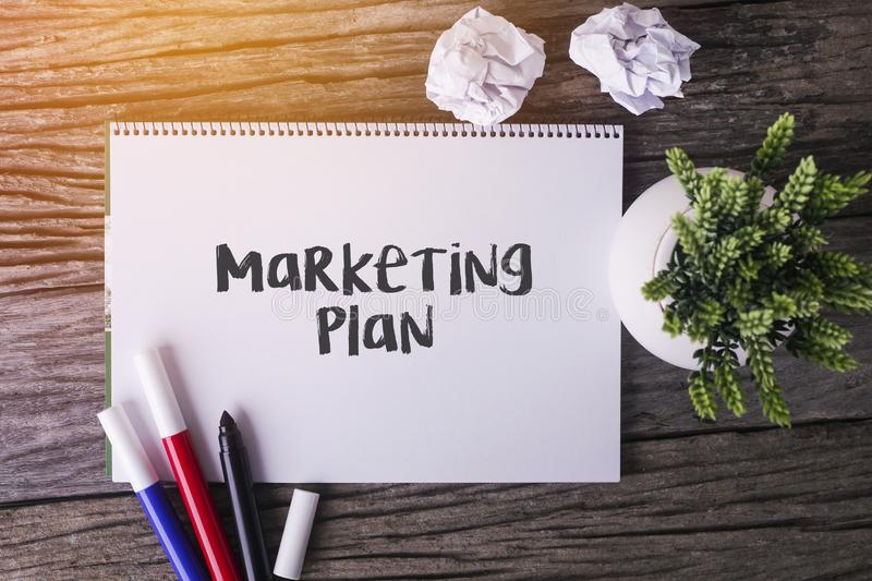 Marketing Plan word with Notepad and green plant on wooden background. royalty free stock photography