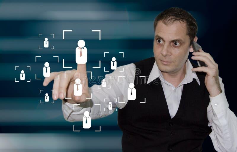 Marketing strategie - zakenman wat betreft persoonspictogram op het virtuele scherm terwijl het hebben van telefoongesprek royalty-vrije stock afbeeldingen