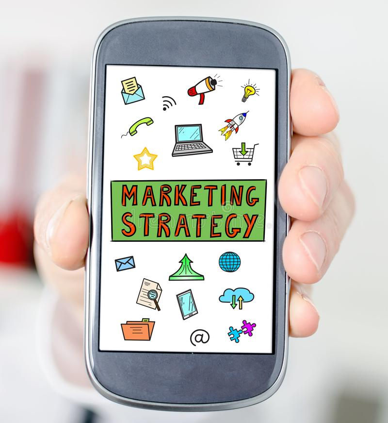 Marketing strategy concept on a smartphone. Hand holding a smartphone with marketing strategy concept stock photo