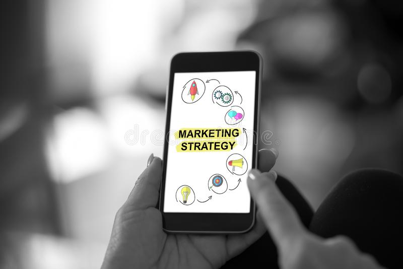 Marketing strategy concept on a smartphone. Hand holding a smartphone with marketing strategy concept royalty free stock photos