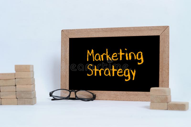 MARKETING STRATEGY inscription on blackboard. Eye glasses and Wood block stacking as step stair stock photo