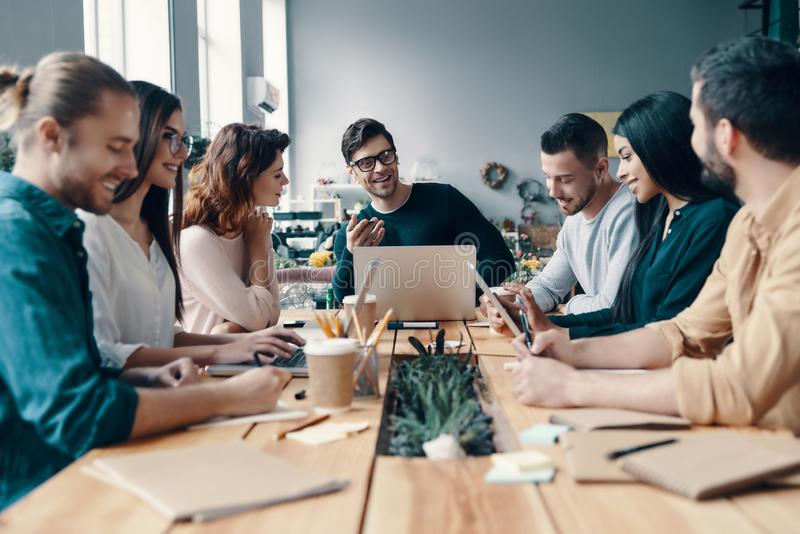 Marketing team. Group of young modern people in smart casual wear discussing something while working in the creative office stock photography
