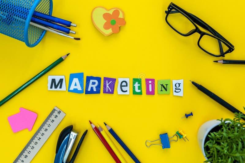 Marketing-Wort aufgebaut mit geschnitztem Buchstaben auf gelbem Arbeitsplatz stockfotografie
