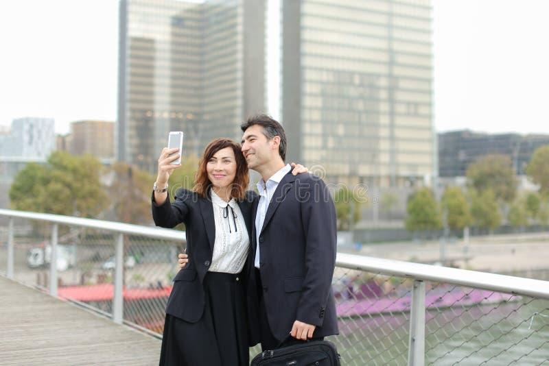 Marketingspezialistmann und Stunden-Managerfrau, die den Smartphone nimmt sel verwendet lizenzfreie stockfotografie