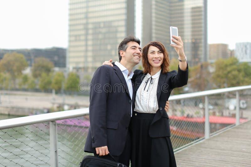 Marketingspezialistmann und Stunden-Managerfrau, die den Smartphone nimmt sel verwendet stockbilder