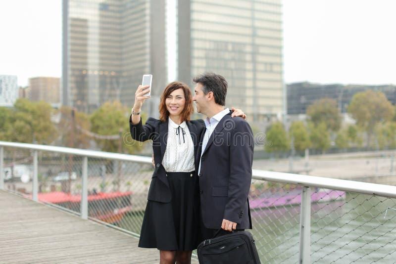 Marketingspezialistmann und Stunden-Managerfrau, die den Smartphone nimmt sel verwendet stockfotografie