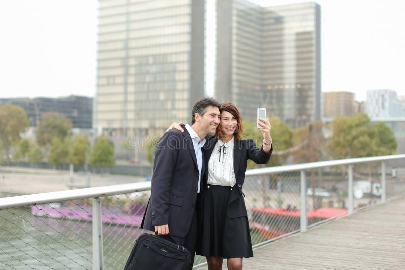 Marketingspezialistmann und Stunden-Managerfrau, die den Smartphone nimmt sel verwendet lizenzfreies stockbild