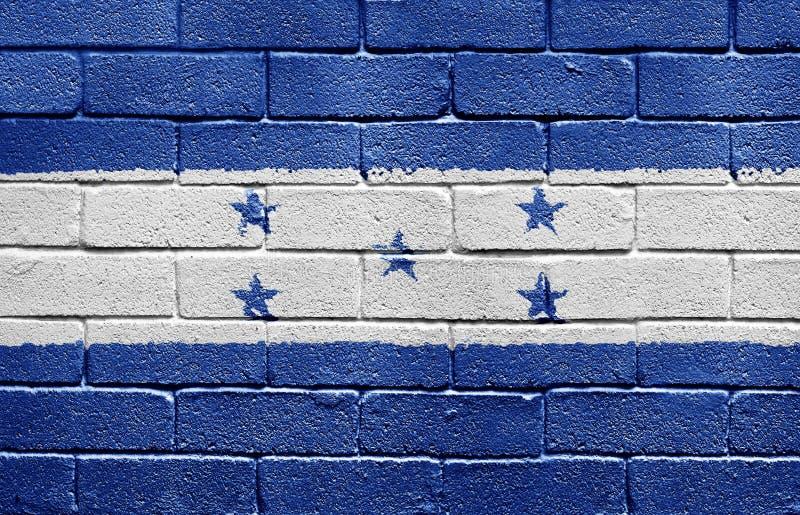 Markierungsfahne von Honduras auf Backsteinmauer lizenzfreies stockbild
